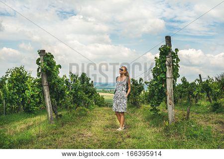 Young woman tourist in dress and sunglusses standing at Tihany wineyards, region of Lake Balaton, Hungary