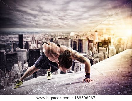 Muscular man is training doing push up above the roof of a building in the city
