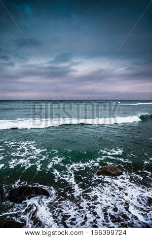 Sunset over the stormy sea in winter