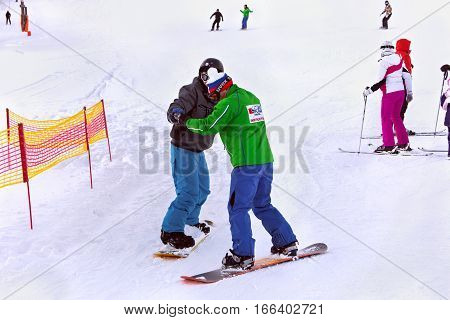SLOVAKIA, STRBSKE PLESO - JANUARY 06, 2015: Snowboarding instructor from Tatra Ski School with a student in Strbske Pleso. The village is a favorite ski and health resort in the High Tatras mountains.