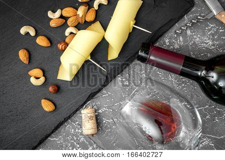 red wine with cheese on dark background top view.