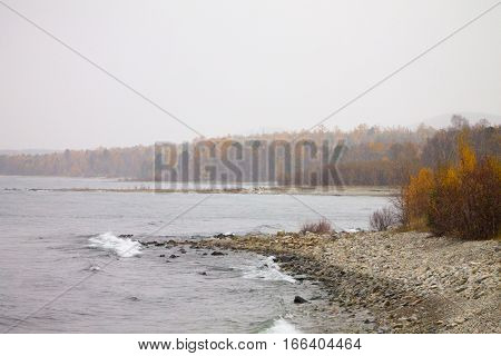 First snow on Lake Baikal, on background waves and colorful landskape