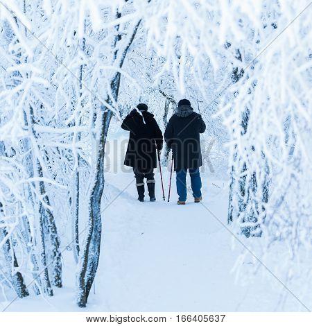 unrecognizable couple walking in a snowy landscape