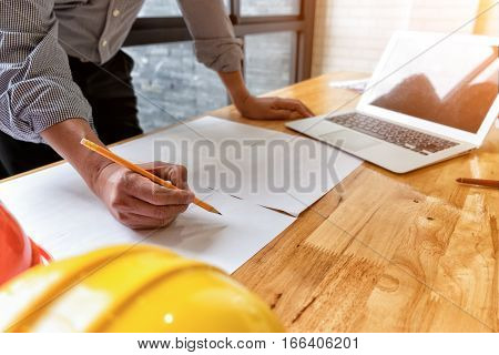 architect drawing architectural project on blueprint with laptop engineering concept architecture concept soft focus vintage tone