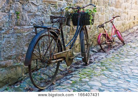 Old Bicycles Leaning Against A Wall