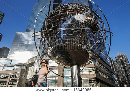 New York, September 10, 2016: A woman is walking by the stainless steel Unisphere sculpture near Time Warner Center.