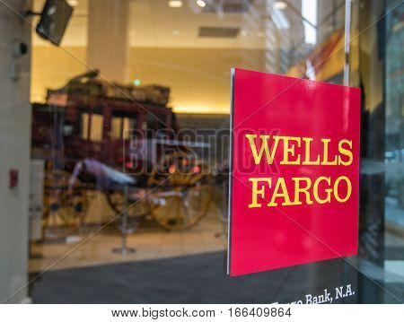New York, September 8, 2016: A Wells Fargo sign at one of their locations in Manhattan. An old coach symbolizing the origins of the company can be seen on the background.