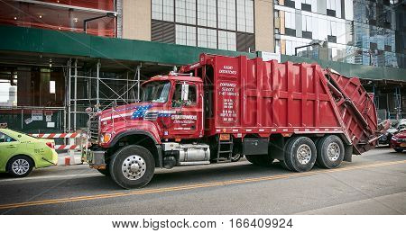 Queens, New York, October 26, 2016: A red garbage truck in the street.