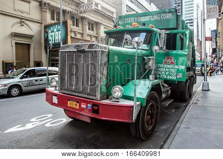 New York, August 2, 2016: A large green garbage truck parked in the streets of Manhattan.