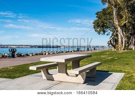 Picnic table and path through Embarcadero Marina Park North, with San Diego bay in the background.