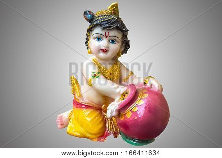 Hindu God Krishna in childhood (Gopal) porcelain statuette isolated in gray background.