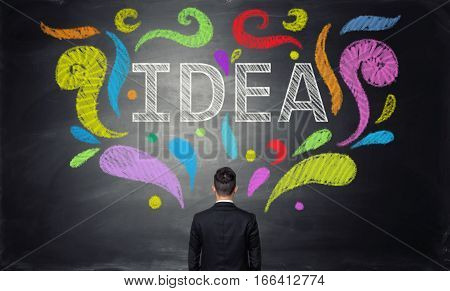 Back view of young businessman wirh colorful light bulb on black background. Creative idea concept. Innovation. Making money