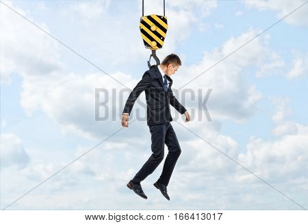 Businessman is being lifted by a crane hook on the background of sky and clouds. Progress concept. Success in business. Money making