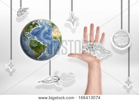 The Earth on a background of small pictures of stars and other cosmic objects and male hand. Damaging the planet. Asteroid close approaching. Reproduction of the space. Elements of this image are furnished by NASA.