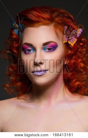 Beautiful young red haired woman with bright colorful makeup and butterflies in hair. Portrait beauty shot. Copy space.