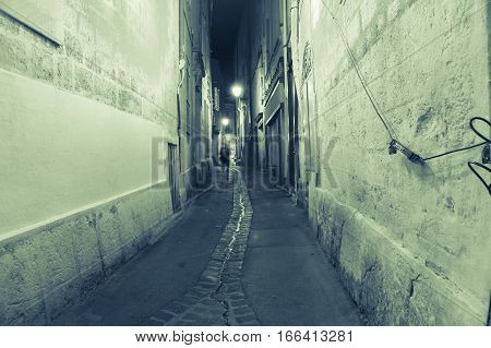 Back street narrow lane in green hues at night Montpellier France urban & architectural