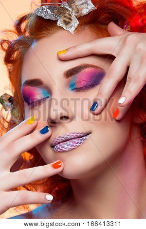 Beautiful young red haired woman with bright colorful makeup and butterflies in hair over orange background. Portrait closeup beauty shot.