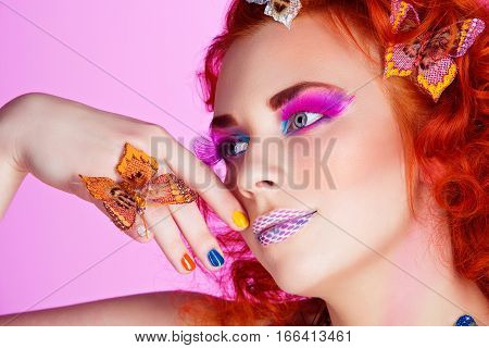 Beautiful young red haired woman with bright colorful makeup covered with butterflies over purple background. Portrait beauty shot. Copy space.