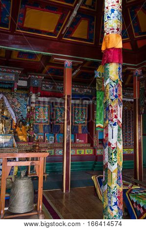 The interior of the Buddhist Arayabal Meditation Temple in Gorkhi-Terelj National Park in Mongolia. Brocade fabric is wrapped around a post and a bell are in the foreground. A statue of Buddha and artwork are in the background.