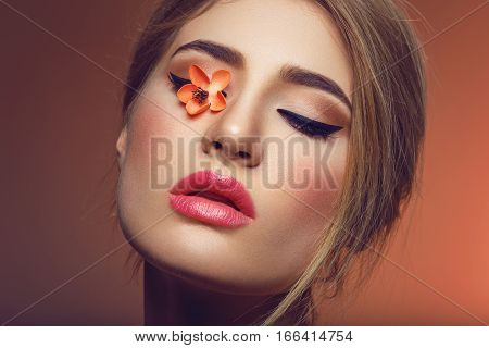 Beautiful young woman with make-up and loose hairdo with artificial orange sakura flower lying on closed eye. Beauty shot on brown background. Copy space.