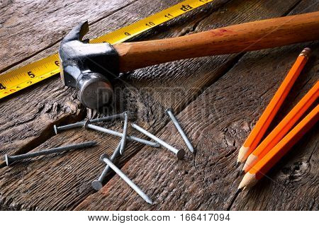 A close up image of an old hammer and nails, yellow tape measure, and several wooden pencils on a workbench.
