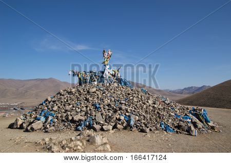 An ovoo made of stones individually placed by worshipers while praying. The obo has a branch on top covered with blue scarves and small flags. Various offerings are on the ovoo.
