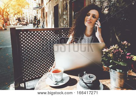 Young beautiful curly brunette calling mobile phone while sitting with portable laptop in street cafe charming dreamy woman using cell telephone and net-book during rest in cafe with cup of tea