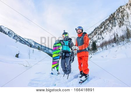 Freeriders Male Skiers And Snowboarders Are In The Mountains In The Snow