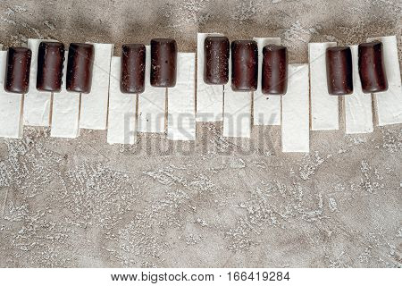Piano Keys Laid Out Chocolates And Marshmallows Paste, On A Neutral Beige Cement Background With Ple