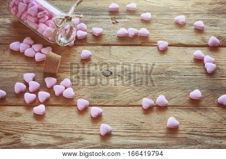 bottle with small pink candy heart shape scattered on old wooden table retro style valentine's day