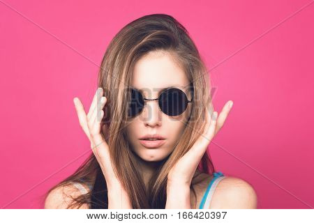 Beautiful fashionable woman in black sunglasses. Pink background. Girl in sunglasses. Round glasses. Toned image.