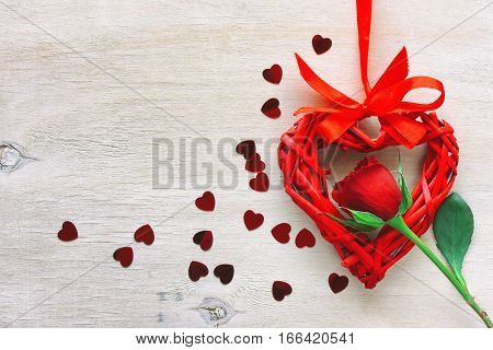 valentine's day red rose wicker heart on silk ribbon confetti on the wooden table