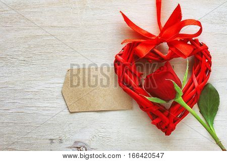 valentine's day red rose wicker heart on scarlet silk ribbon paper label on a wooden table