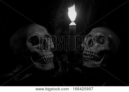 Two Skull And The Candle On Old Wooden Table In The Cemetery With Black Background In Night Time  /