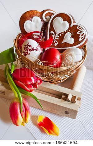 Traditional Czech easter decoration - homemade gingerbread hearts cakes with tulip flowers painted eggs and ratchet on white background. Spring easter holiday arrangement.