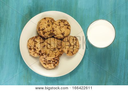 A plate of chocolate chips cookies, shot from above on a vibrant blue background, with a glass of milk and copy space