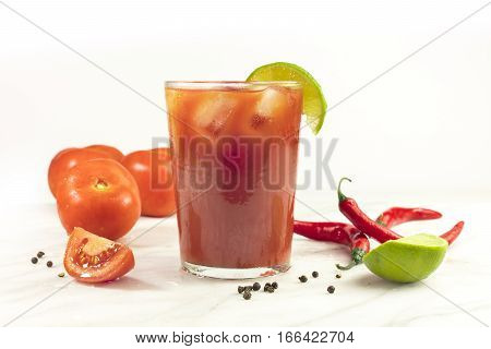 Bloody Mary cocktail with red hot chili peppers, slices of lime, tomatoes, and copyspace