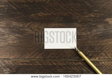 An overhead photo of a blank white thick cardboard business card on a dark wooden background texture with a golden ink pen. A mockup or a minimalist banner with copyspace