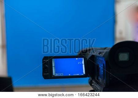 video camera in a studio focused on blue background stock photo