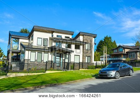 Brand new luxury house with a car parked on the road in front