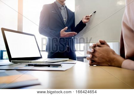 Businesswoman asking question during her colleagues presentation in bright office.