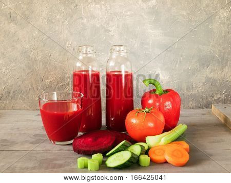 Fresh juice from vegetables tomato pepper celery carrots cucumber beets poured into small glass bottles which stand side by side on grey wooden table. Horizontal arrangement front view