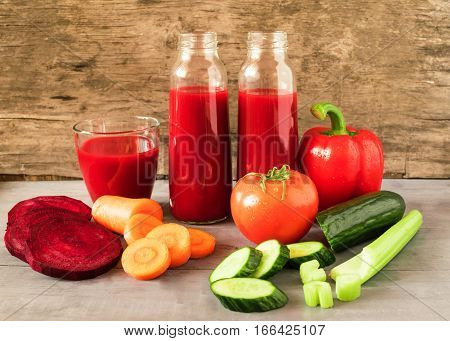 Fresh vegetables juice poured in a glass small bottle on a gray wooden background. Horizontal arrangement front view.