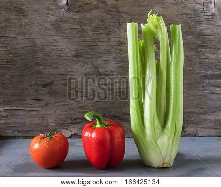 Group of vegetables tomato pepper celery on a gray wooden background. Horizontal arrangement front view.