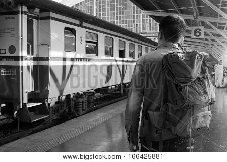 Asian young man traveler with backpack on a platform in the railway or train station. Train travel concept.