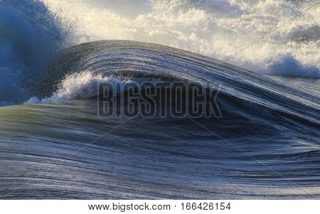 Blue ocean storm wave with texture and power crashes at sea.