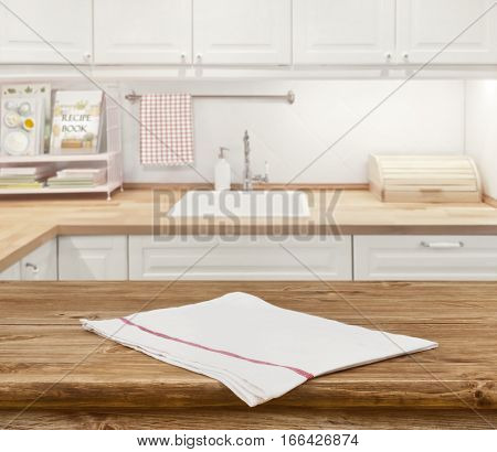 Wooden dinning table with napkin in front of blurred kitchen