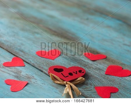 Valentines Day background with hearts on old wooden table, side view.