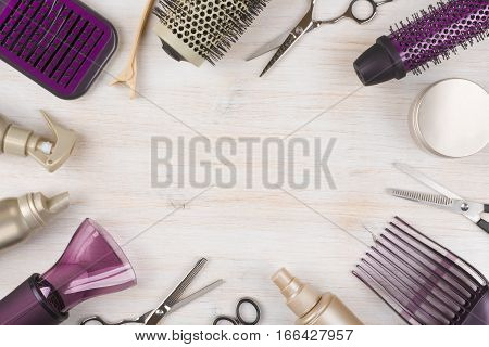 Hairdresser tools on wooden background with copy space in center