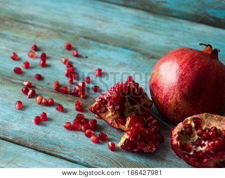 Fresh Pomegranate fruit with seeds on old table, side view